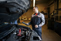 O mecânico que usa o impulsionador cabografa à partida um motor de automóveis fotografia de stock royalty free