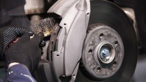 O mecânico que usa uma escova de fio limpa o lugar para pastilhas dos freios do carro video estoque