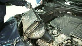 O mecânico realiza trabalhos sob a capa com motor do seis-cilindro filme
