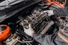 O mec?nico toma ? cabe?a de motor das partes Repara??o do motor diesel, das m?os dos trabalhadores e da ferramenta modernos imagens de stock royalty free