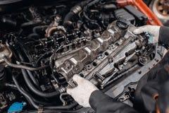 O mec?nico toma ? cabe?a de motor das partes Repara??o do motor diesel, das m?os dos trabalhadores e da ferramenta modernos fotos de stock royalty free