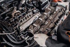 O mec?nico toma ? cabe?a de motor das partes Repara??o do motor diesel, das m?os dos trabalhadores e da ferramenta modernos imagem de stock royalty free