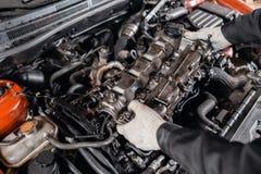 O mec?nico toma ? cabe?a de motor das partes Repara??o do motor diesel, das m?os dos trabalhadores e da ferramenta modernos fotografia de stock royalty free