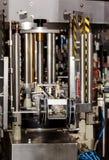 O mecanismo da máquina tampando da garrafa automática Fábrica para a produção de bebidas alcoólicas Fotografia de Stock