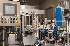 O mecanismo da máquina tampando da garrafa automática Fábrica para a produção de bebidas alcoólicas Foto de Stock