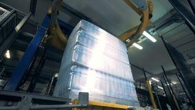 O mecanismo industrial redondo está envolvendo blocos de garrafas de cerveja no polietileno vídeos de arquivo