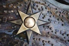 O medalhão das pontas da estrela oito do emblema do ferro com coordenadas polares no metal molhado decorou o fundo Imagens de Stock