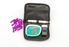 O medidor da glicemia, o valor do açúcar no sangue é medido em um bloco do dedo na caixa preta no fundo branco Foto de Stock Royalty Free