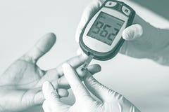 O medidor da glicemia, o valor do açúcar no sangue é medido em um fing fotos de stock