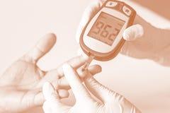 O medidor da glicemia, o valor do açúcar no sangue é medido em um fing imagem de stock royalty free