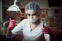 O medo do tratamento dental A menina do dentista das crianças no escritório do dentista mantém o instrumento e os sustos foto de stock royalty free