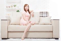 O meio atrativo e bonito envelheceu a mulher que senta-se no sofá e que relaxa em casa menopause Fotos de Stock Royalty Free