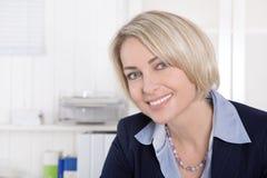 O meio atrativo envelheceu a mulher no equipamento do negócio que senta-se em seu o imagens de stock royalty free