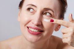 O meio bonito envelheceu a mulher que aplica o tratamento de creme cosmético na cara no fundo cinzento Zombaria ascendente e espa Fotos de Stock Royalty Free
