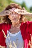 O meio de incandescência envelheceu a mulher com as sardas que sofrem da dor de cabeça Fotos de Stock Royalty Free