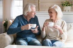 O meio de sorriso dos pares envelheceu os povos que sentam-se no chá bebendo do sofá fotos de stock