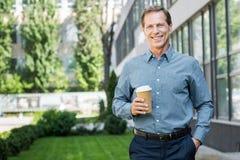 o meio de sorriso envelheceu o homem de negócios que está com a xícara de café descartável perto do escritório imagem de stock