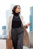 O meio de sorriso envelheceu a morena em um revestimento brilhante e em uma calças cinzenta Imagem de Stock Royalty Free