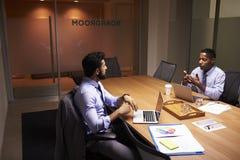 O meio dois envelheceu o homem de negócios que trabalha tarde em um escritório fotografia de stock royalty free