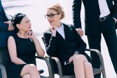 O meio envelheceu as mulheres de negócios que falam ao sentar-se em cadeiras entre dois homens de negócios Fotografia de Stock