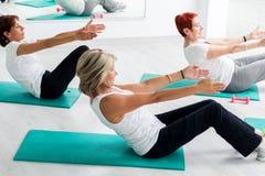 O meio envelheceu as mulheres que fazem o exercício abdominal no gym imagens de stock