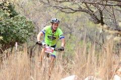 O meio envelheceu a equitação masculina através do arbusto na raça do Mountain bike Fotografia de Stock Royalty Free
