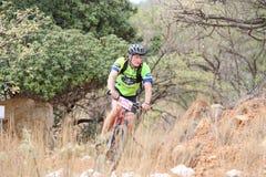 O meio envelheceu a equitação masculina através do arbusto na raça do Mountain bike Fotografia de Stock