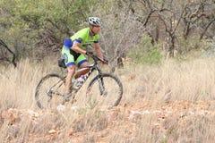 O meio envelheceu a equitação masculina através do arbusto no Mountain bike de Mathaithai Fotos de Stock Royalty Free