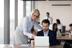 O meio envelheceu o gerente executivo que ajuda ao colega masculino imagens de stock royalty free