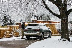 O meio envelheceu o homem com o carro coberto de neve na entrada de automóveis no dia extremamente nevado com queda da neve fotos de stock