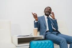 o meio envelheceu o homem de negócios que fala pelo smartphone ao esperar Fotografia de Stock