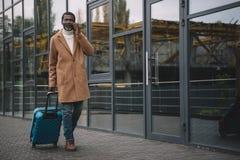 O meio envelheceu o homem que anda em uma rua com um saco e uma fala rodados Fotografia de Stock Royalty Free