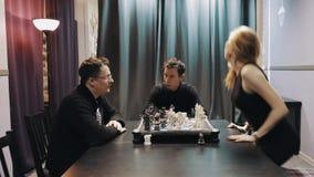 O meio envelheceu o homem que joga a xadrez com mulher que anda afastado enquanto um outro homem anda dentro vídeos de arquivo