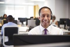 O meio envelheceu o homem que trabalha no computador com os auriculares no escritório fotografia de stock royalty free