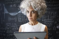 O meio envelheceu a mulher acadêmico que usa a tabuleta que olha à câmera imagens de stock