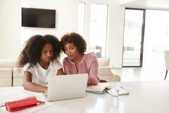 O meio envelheceu a mulher afro-americano que ajuda sua filha adolescente com trabalhos de casa, vista dianteira imagens de stock
