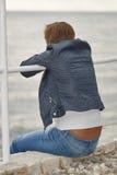 O meio envelheceu a mulher caucasiano que senta-se na praia do mar Imagens de Stock
