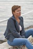 O meio envelheceu a mulher caucasiano que senta-se na praia do mar Fotografia de Stock Royalty Free