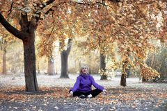 O meio envelheceu a mulher caucasiano senta-se apenas sob a árvore grande no parque do outono na pose da meditação com olhos fech imagens de stock royalty free