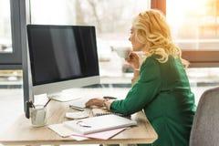o meio envelheceu a mulher de negócios que usa o computador de secretária com tela vazia e bebendo o café foto de stock