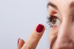 O meio envelheceu a mulher que aplica ou que põe a lente de contato para a visão em seu olho marrom pelo dedo Fim ascendente e is Fotografia de Stock