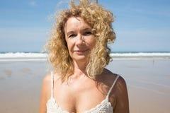 O meio envelheceu a mulher que descansa na praia perto do mar Fotografia de Stock