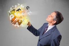 O meio envelheceu o homem de negócios que guarda o portátil com letras coloridas Fotografia de Stock Royalty Free