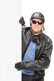 O meio envelheceu o homem no casaco de cabedal atrás de um painel Fotografia de Stock