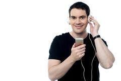 O meio envelheceu o homem que aprecia a música em seu móbil Fotos de Stock Royalty Free