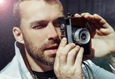 O meio envelheceu o homem que fotografa na câmera retro, dia, exterior Fotografia de Stock