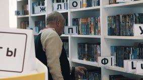 O meio envelheceu o homem que pegara registra para fora caixas de livro da biblioteca vídeos de arquivo