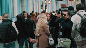 O meio envelheceu o turista nos óculos de sol que tomam a foto no passeio em horas de ponta da cidade vídeos de arquivo