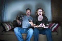 O meio envelheceu os pares e o cão que riem da televisão Fotografia de Stock Royalty Free