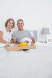 O meio envelheceu os pares que comem o café da manhã na cama junto Fotografia de Stock Royalty Free